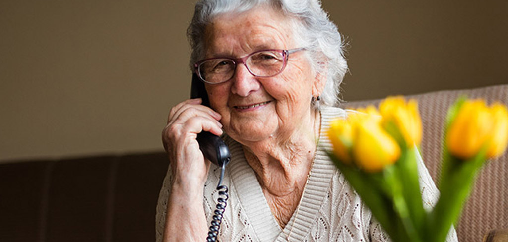 elderly woman sitting in a chair on an old fashioned chorded telephone