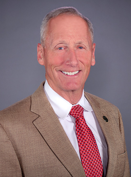 Portrait of Rick Lee wearing a tan jacket with white shirt and red tie