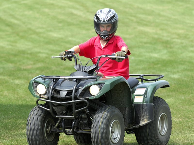 young boy in red shirt riding ATV vehicle
